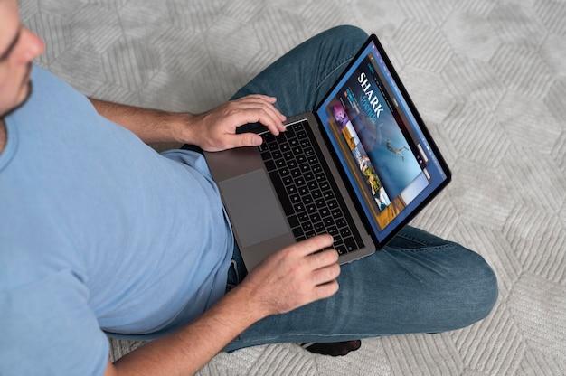 집에서 디지털 비서와 함께 노트북을 사용하는 남자