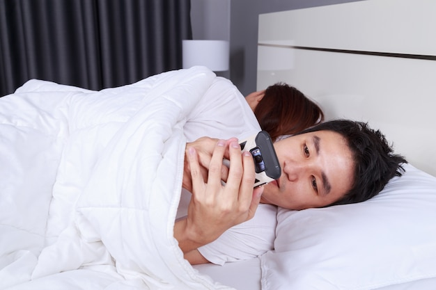 Man using his mobile phone in bed while his wife is sleeping next to him