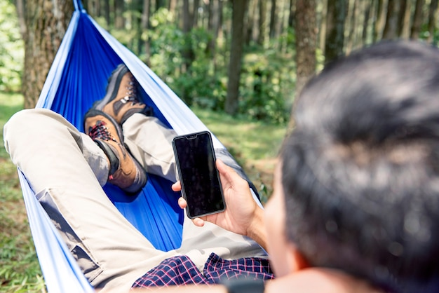 Man using his mobile phone while relaxing in hammock
