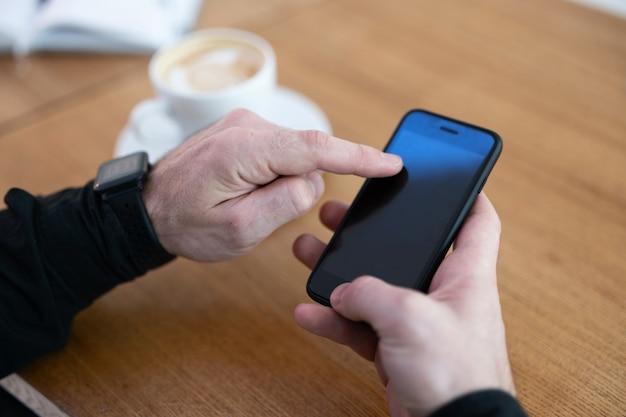 コーヒーショップで彼の電話を使用している男。空白のコピースペース画面を備えたスマートフォン。カプチーノまたはフラットホワイトのカップと木製のテーブルの上の日記を開きます。スマートフォンを抱きしめる男の手。