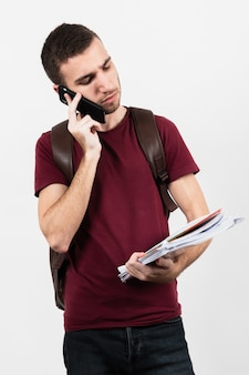 Man using his phone and looking at his notes