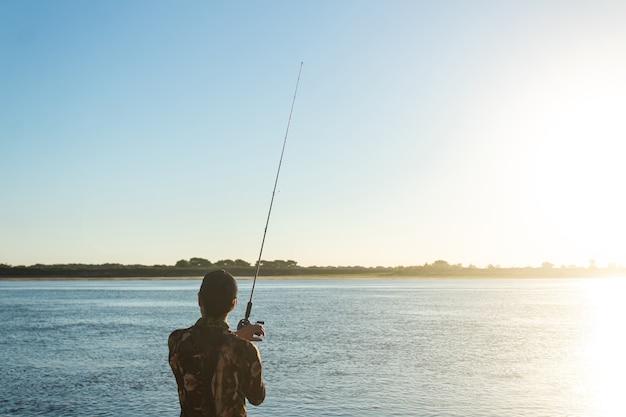 Человек с удочкой ловит рыбу в реке.