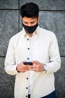 Мужчина использует свой смартфон в защитной маске от пандемии коронавируса covid 19