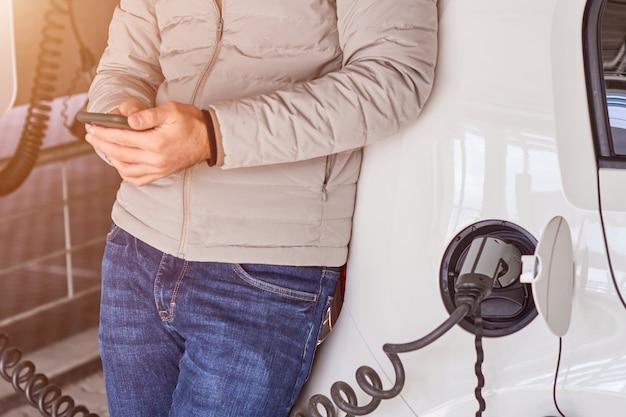 Человек, используя его смартфон во время зарядки электромобиля в точке зарядки на солнечном свете
