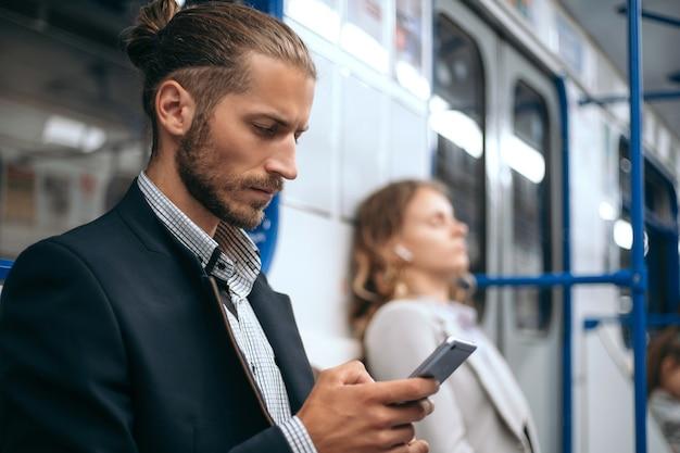 電車の地下鉄に座ってスマートフォンを使用している男性