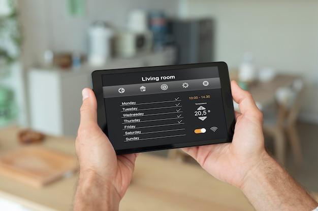 Человек, использующий свой планшет для приложения домашней автоматизации