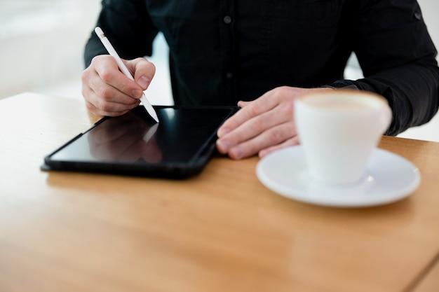 スタイラスでタブレットを使用している男性。ガジェットのオピースペース画面。彼の前にコーヒーとタブレットのカップと一緒に座っている黒い服を着た男のクローズアップビューをカットします。
