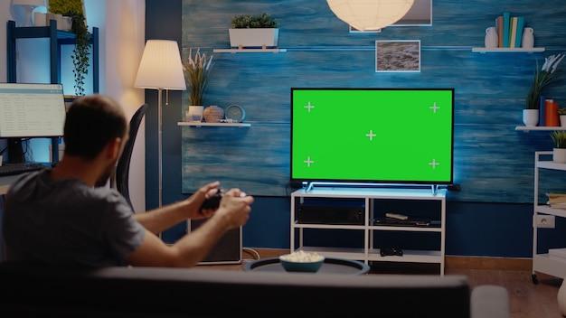 緑の画面の背景表示でジョイスティックを使用している男