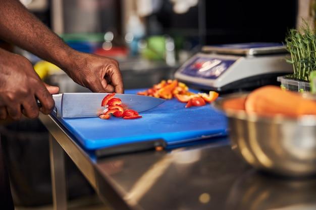 식당 요리를 위해 고추 조각을 만들기 위해 칼과 보드를 사용하는 사람