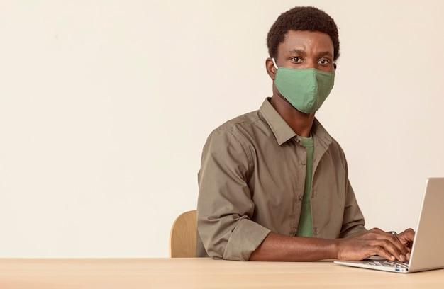 ノートパソコンを使用し、緑の医療マスクを着用している男性