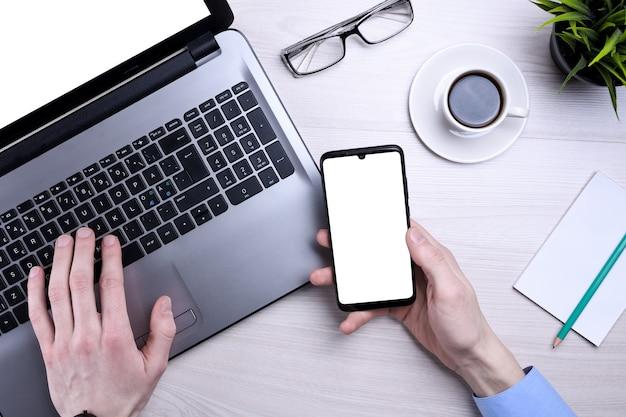 自宅の居間でノートパソコンを使用している男性。成熟したビジネスマンは、電子メールを送信し、在宅勤務します。在宅勤務。書類や書類をテーブルに置いてコンピューターに入力します。
