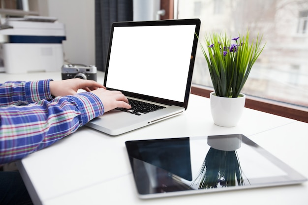 Man using laptop computer next to a city window with tablet pc and a retro camera on a table