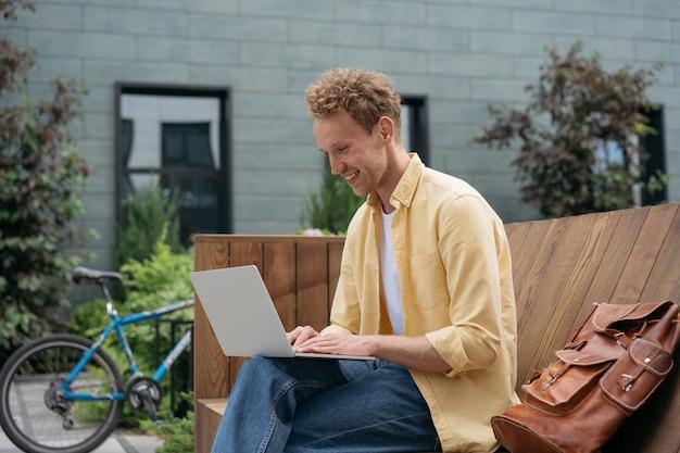 ラップトップコンピューターを使用して、屋外でオンラインで作業しているプログラマーの笑顔のキーボードで入力