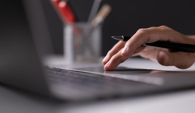 사무실 복사 공간에 있는 책상에서 새로운 프로젝트 아이디어를 작업하는 노트북 컴퓨터를 사용하는 남자
