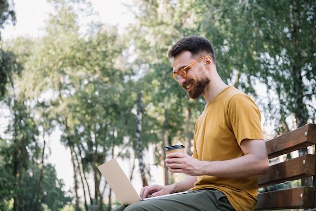 ラップトップを使用して、一杯のコーヒーを保持している、ベンチに座っている男。公園で働くフリーランサーのコピーライター