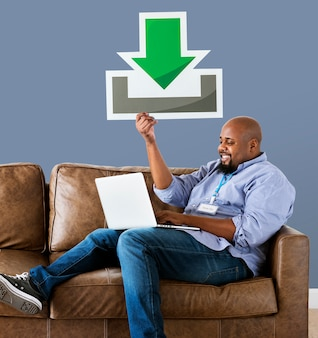 Man using a laptop and holding a download icon