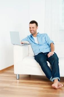 Uomo che utilizza un computer portatile a casa