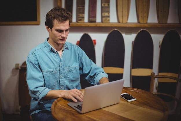 店でラップトップを使用している男