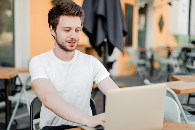 Man using laptop for remote work in cafe