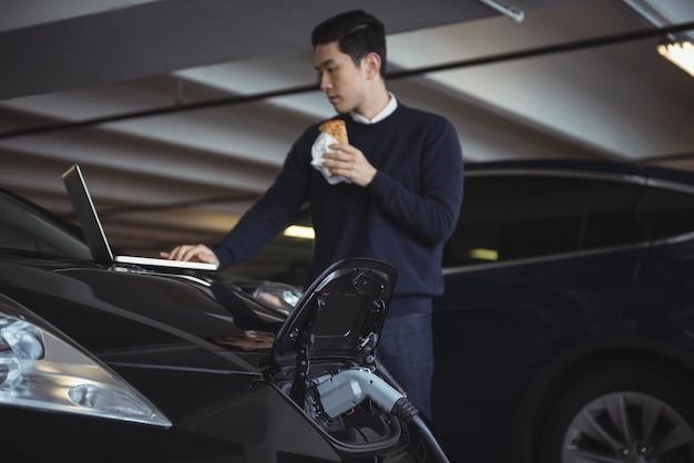 Uomo che utilizza computer portatile durante la ricarica di auto elettriche