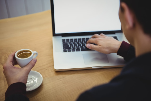 Человек, использующий ноутбук во время кофе
