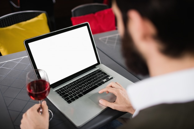 Uomo che per mezzo del computer portatile mentre mangiando bicchiere di vino