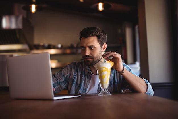 Человек, использующий ноутбук во время молочного коктейля