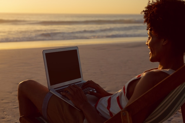 Man using laptop while relaxing in a beach chair on the beach