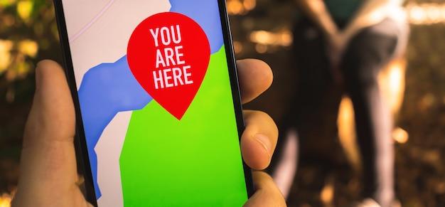 숲에서 탐색을 위해 휴대 전화의 지도를 사용하는 남자. 야외 하이킹 및 여행 배너 컨셉 사진