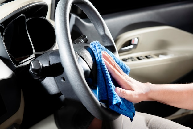 Man using microfiber cloth to cleaning car interior
