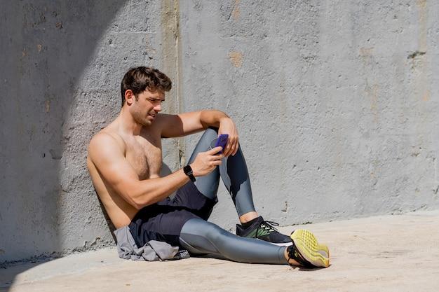 Человек с помощью мобильного телефона после тренировки сидит на полу без рубашки
