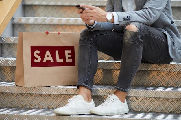 Человек с помощью мобильного приложения во время покупок