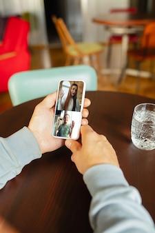 Человек использует мобильный телефон для видеозвонка, попивая воду