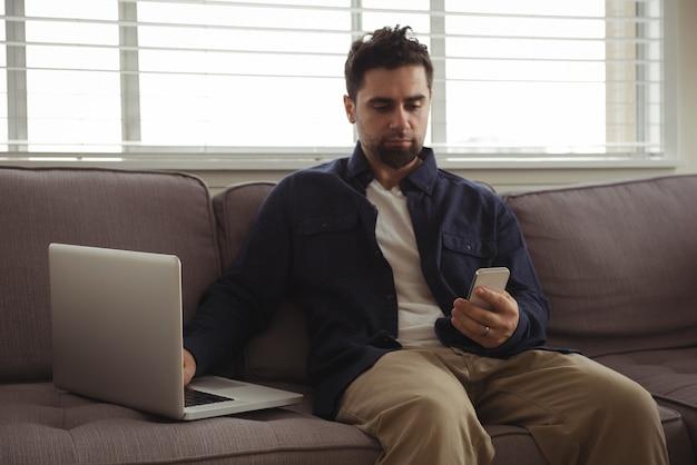 ソファで携帯電話とノートパソコンを使用している男