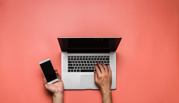 パステルピンクの背景に携帯電話とラップトップを同時に使用している人