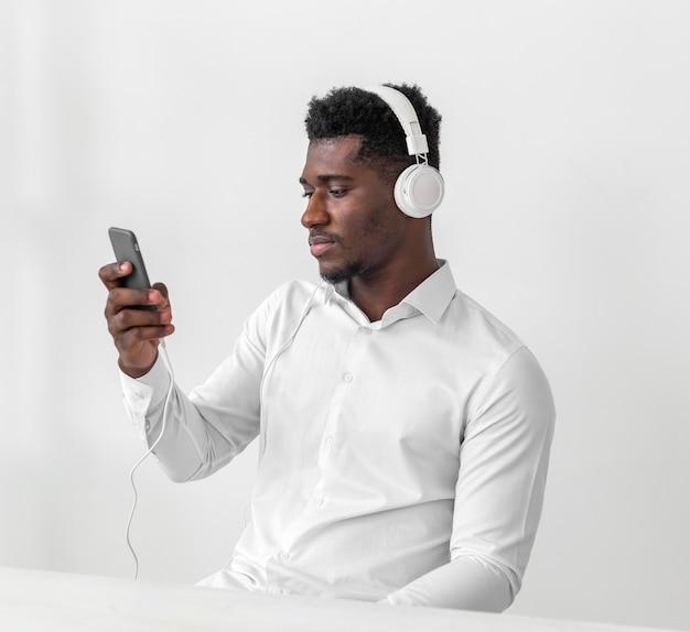 携帯電話を使用して音楽を聴いている男性