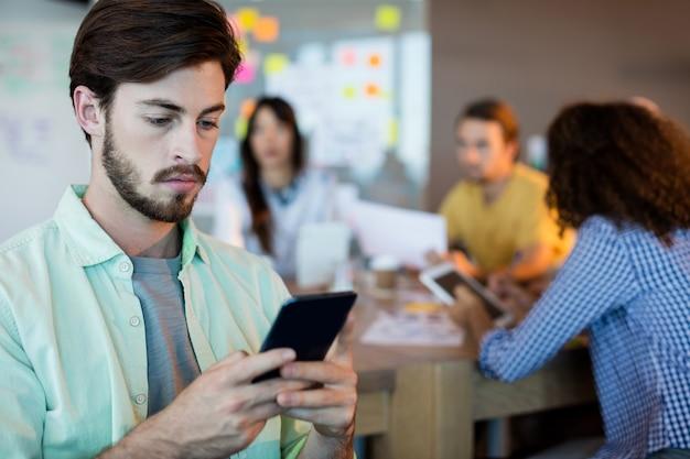 Человек, использующий мобильный телефон в офисе