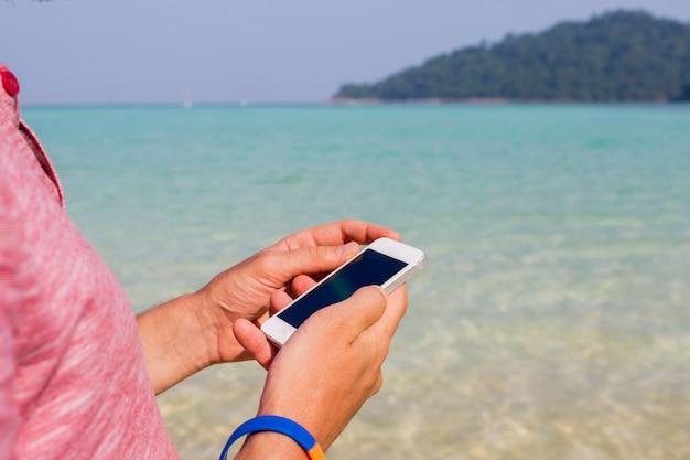 Человек, использующий мобильный телефон на пляже