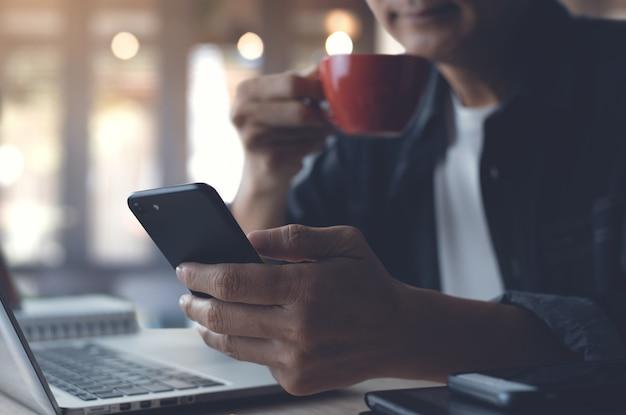コーヒーショップで働いているときに携帯電話を使用している男性