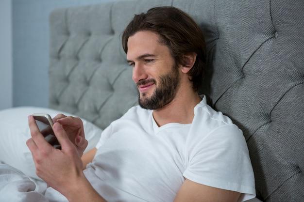 Человек с помощью мобильного телефона в спальне