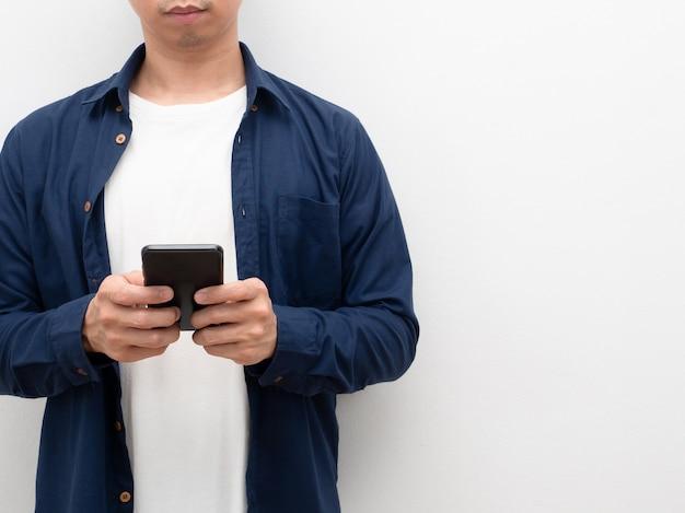 コピースペースの白い背景で彼の手作物の体に携帯電話を使用している男