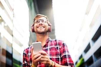 Man using mobile phone listening music wearing headphones