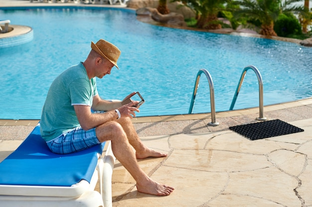 Man using mobile phone on vacation by the pool in hotel, concept of a freelancer working for himself