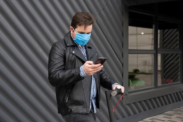 電動スクーターに医療マスクを身に着けている携帯電話を使用している人