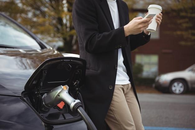 車の充電中に携帯電話を使用している男性