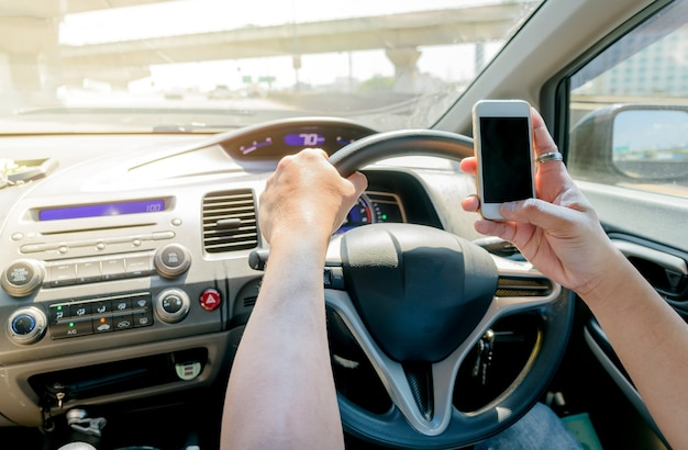 Man using mobile phone while driving a car on expressway