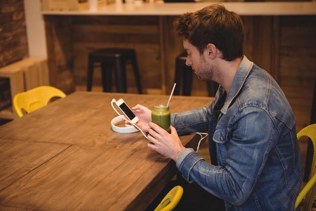 Man using mobile phone while having juice