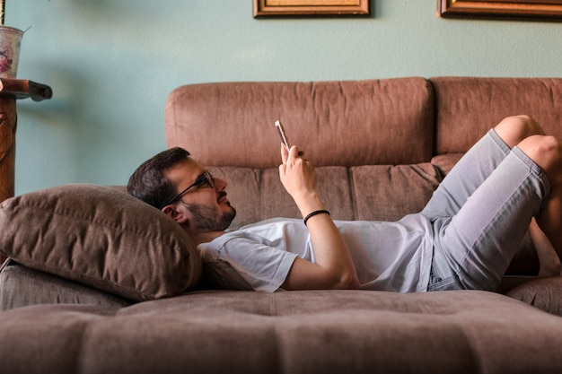 Man using mobile phone while lying on sofa at home