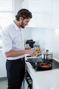Man using mobile phone while preparing food in kitchen