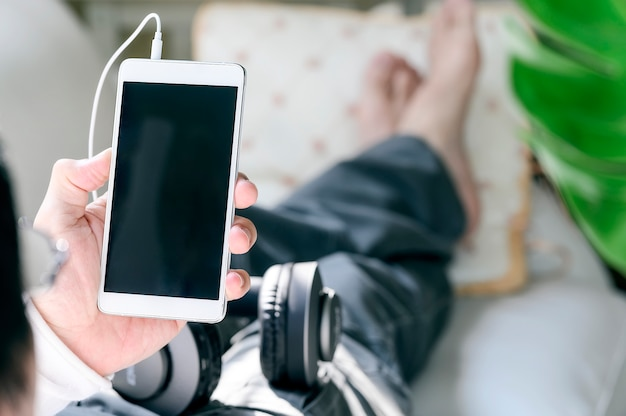 Man using mobile phone while relaxing at home